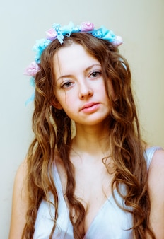 Porträt eines schönen mädchens mit wallendem haar und einem blumenkranz auf dem kopf