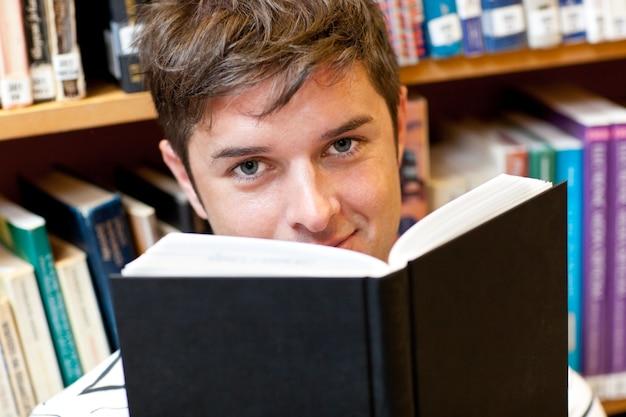 Porträt eines schönen männlichen studenten, der ein buch sitzt auf dem boden liest