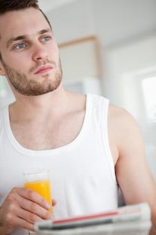 Porträt eines schönen mannes, der orangensaft beim lesen der nachrichten trinkt