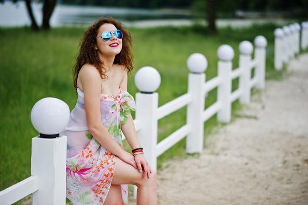 Porträt eines schönen modells, das gegen den zaun in der sonnenbrille im seeufer aufwirft.