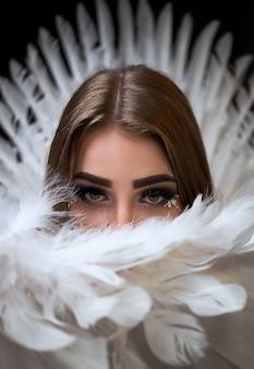 Porträt eines schönen modells mit weißen flügeln. hintergrund ist schwarz