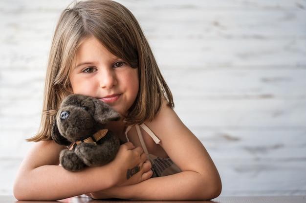Porträt eines schönen, nachdenklichen, gelangweilten kleinen mädchens mit ihrem lieblingsspielzeug, das träumt und ideen in ihrem kopf kreiert. kreativer vorgang. weicher fokus