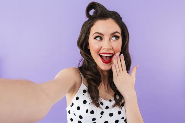 Porträt eines schönen pin-up-mädchens mit hellem make-up, das isoliert über einer violetten wand steht und ein selfie macht