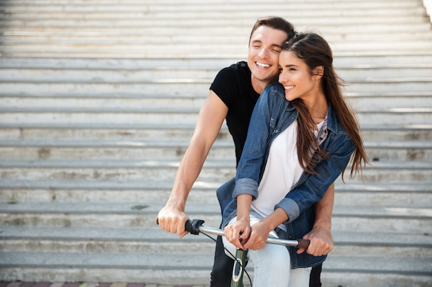 Porträt eines schönen reizenden paares, das auf einem fahrrad reitet