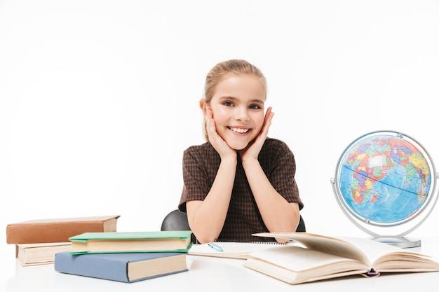 Porträt eines schönen schulmädchens, das bücher liest und hausaufgaben macht, während es am schreibtisch in der klasse sitzt, isoliert über weißer wand