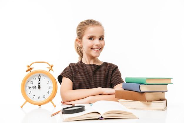 Porträt eines schönen schulmädchens mit großem wecker auf dem schreibtisch, das bücher in der klasse studiert und liest, isoliert über weißer wand