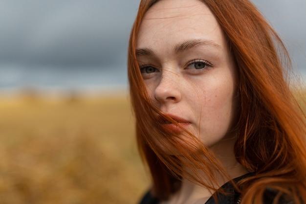 Porträt eines schönen sinnlichen mädchens mit langen roten haaren, das in der natur steht und direkt in die kamera schaut. hochwertiges foto