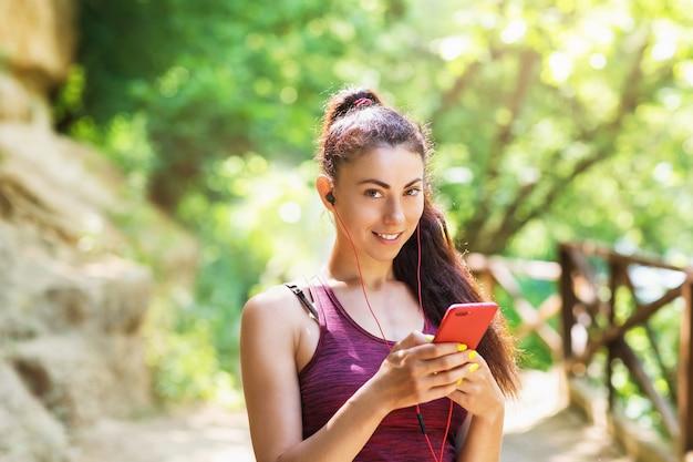 Porträt eines schönen sportmodells im park mit einem telefon in der hand