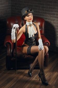 Porträt eines schönen steampunk-mädchens in dessous und strümpfen, die im alten sessel sitzen.