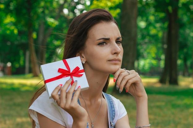 Porträt eines schönen teenagers mit nachdenklichem kleinen geschenk in der hand
