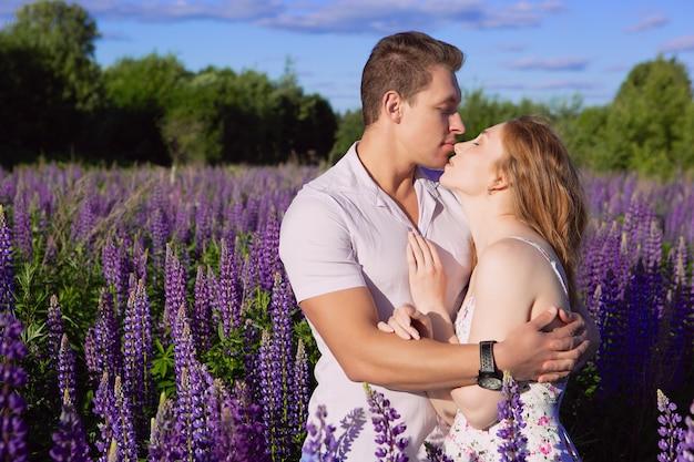 Porträt eines schönen verliebten paares, das sanft auf einem blühenden lupinenfeld küsst