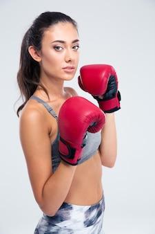 Porträt eines schönen weiblichen boxers, der lokalisiert auf einer weißen wand steht