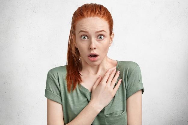 Porträt eines schönen weiblichen modells mit bugged eyed und angehaltenem atem, hat einen roten pferdeschwanz, ist kaual gekleidet, kann nicht an augen glauben, fühlt sich verängstigt und fassungslos, isoliert über weiß