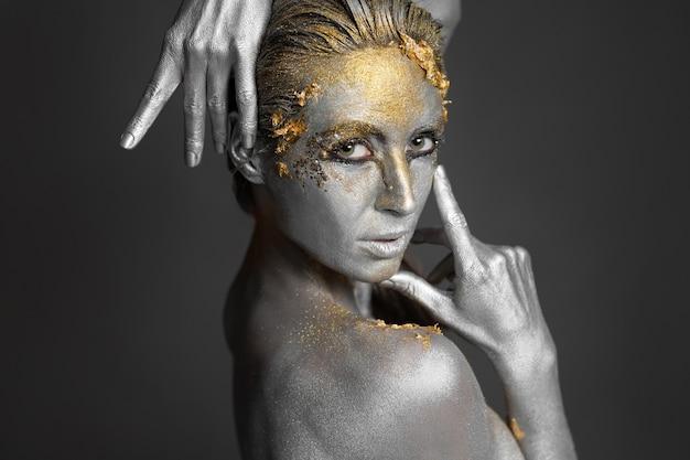 Porträt eines schönen weiblichen modells mit gold- und silberfarbe auf haut und haaren im studio.