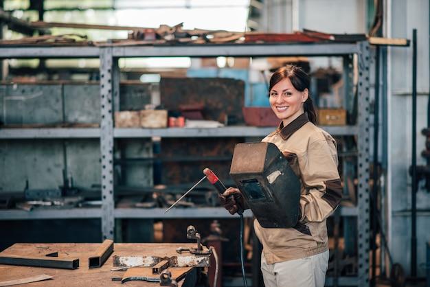 Porträt eines schönen weiblichen schweißers an der schwerindustriefabrik.