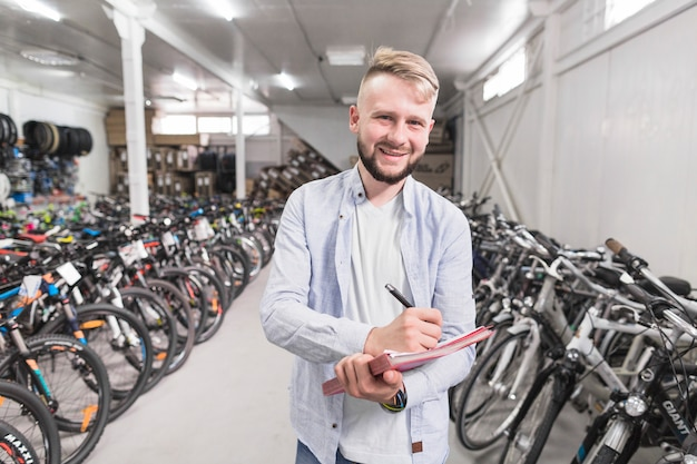Porträt eines schreibens des glücklichen mannes auf dokument im fahrradshop