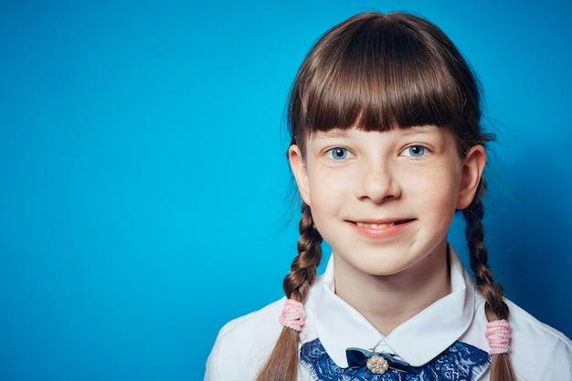 Porträt eines schulmädchenmädchens auf einem blauen hintergrund