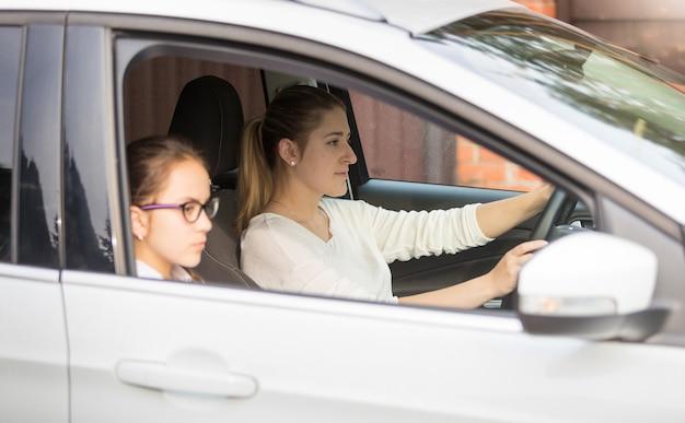 Porträt eines schulmädchens, das mit der mutter mit dem auto zur schule fährt