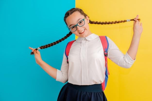 Porträt eines schulmädchens in den gläsern mit buchlehrbüchern auf gelbem blau