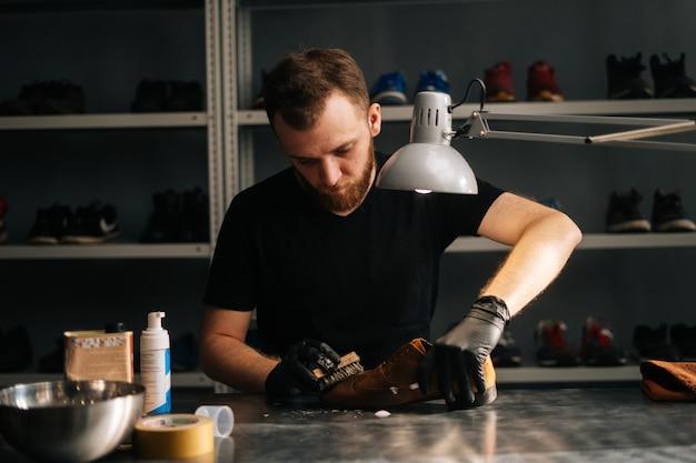 Porträt eines schusters, der reinigungsschaum auf alte, abgenutzte hellbraune lederschuhe aufträgt, die repariert werden sollen