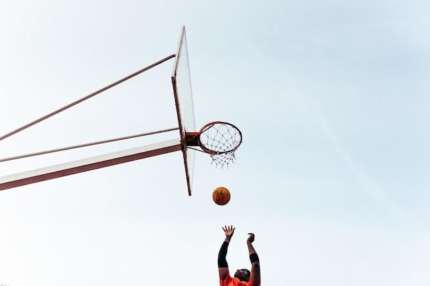 Porträt eines schwarzen afro-jungen, der in den korb springt, um den ball zu schießen. basketball spielen auf einem städtischen platz