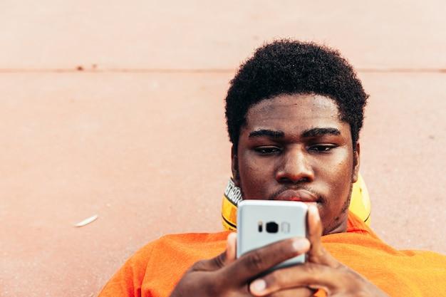 Porträt eines schwarzen afroamerikanischen jungen, der auf seinem basketball liegt und mit seinem handy auf einem städtischen basketballplatz navigiert. mit einem orangefarbenen t-shirt bekleidet.