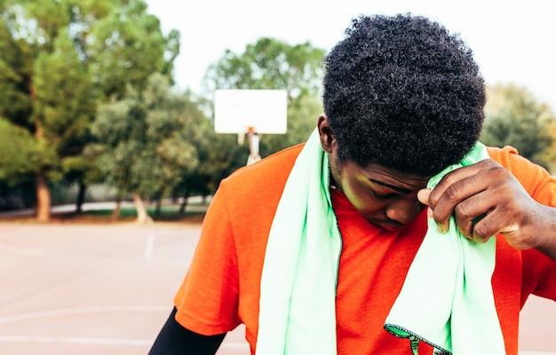 Porträt eines schwarzen afroamerikanischen jungen, der seinen schweiß mit einem grünen handtuch auf einem städtischen basketballplatz von seiner stirn trocknet.
