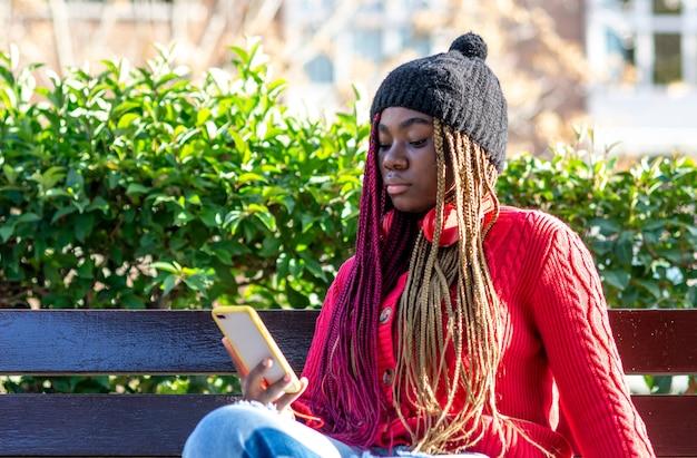 Porträt eines schwarzen mädchens mit farbigen zöpfen, die auf einer bank sitzen und ihr telefon benutzen. gekleidet in einen roten pullover und eine schwarze wollmütze.