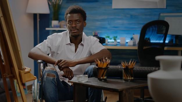 Porträt eines schwarzen mannes mit behinderung, der an einer leinwandzeichnung arbeitet