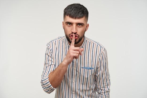 Porträt eines schweren jungen kurzhaarigen bärtigen mannes, der die augenbrauen runzelt und den zeigefinger auf den lippen hält, während er darum bittet, ruhig zu sein, isoliert über der weißen wand