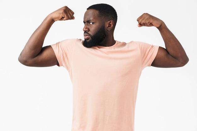 Porträt eines selbstbewussten afrikanischen mannes mit t-shirt, der isoliert über weißer wand steht und bizeps beugt