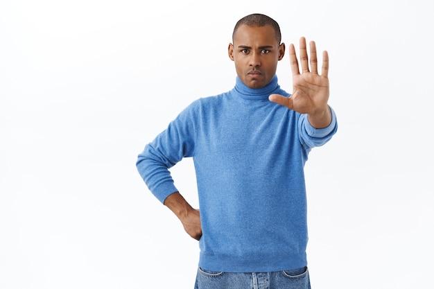 Porträt eines selbstbewussten, ernst aussehenden jungen mannes, der als sicherheit warnt, hand in anschlag nach vorne strecken