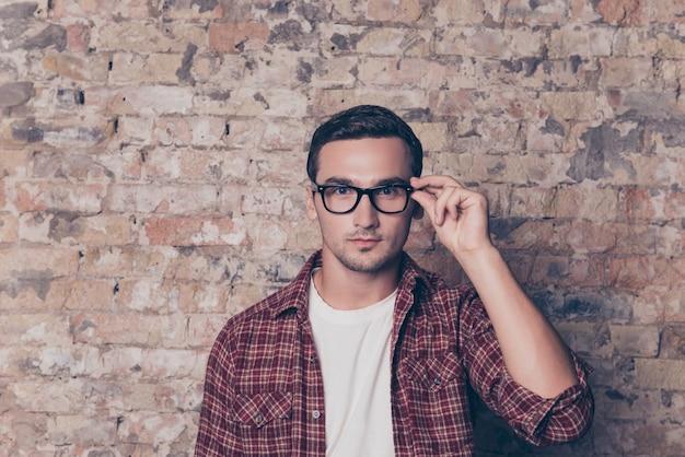 Porträt eines selbstbewussten ernsthaften klugen mannes, der seine brille berührt