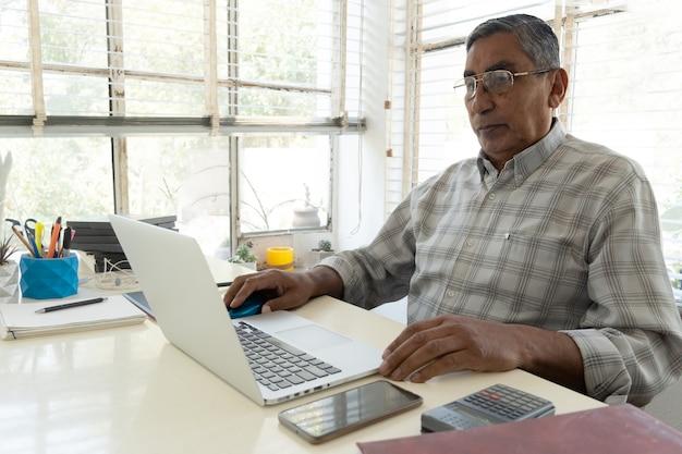 Porträt eines selbstbewussten geschäftsmannes mit laptop am schreibtisch im büro