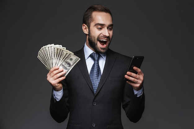 Porträt eines selbstbewussten gutaussehenden geschäftsmannes, der anzug isoliert trägt, zeigt geldbanknoten, unter verwendung des mobiltelefons