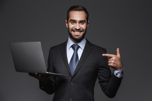 Porträt eines selbstbewussten gutaussehenden geschäftsmannes, der anzug lokalisiert hält und laptop-computer hält
