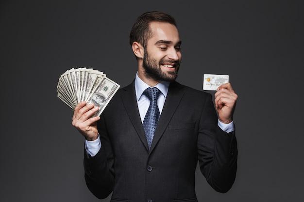 Porträt eines selbstbewussten gutaussehenden geschäftsmannes, der einen anzug trägt, der isoliert steht, geldbanknoten zeigt, plastikkreditkarte hält