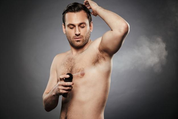 Porträt eines selbstbewussten hemdlosen mannes, der deodorant sprüht