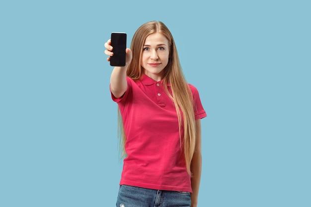 Porträt eines selbstbewussten lässigen mädchens, das handy des leeren bildschirms lokalisiert über blauem hintergrund zeigt.