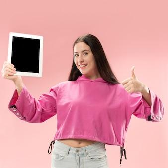 Porträt eines selbstbewussten lässigen mädchens, das leeren bildschirm des laptops lokalisiert über rosa hintergrund zeigt.