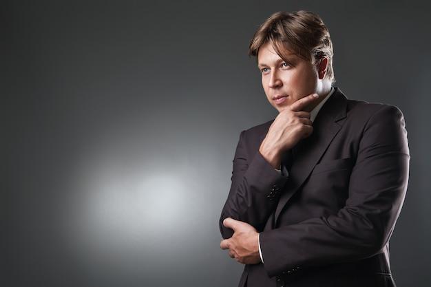 Porträt eines selbstbewussten mannes, der in anzug denkt