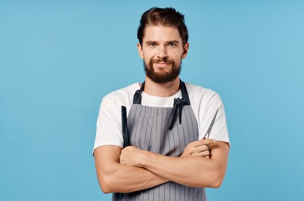 Porträt eines selbstbewussten mannes in einem grauen schürzenfriseurkammfrisurmodell.