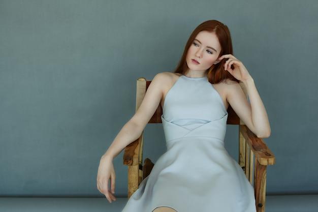 Porträt eines selbstbewussten rothaarigen mädchens, das einen prüfenden blick auf die wand des kopierraums hat und auf einem stuhl sitzt. wunderschönes weibliches modell, das blaues kleid trägt, das sich ausruht und aufwirft