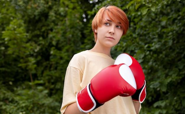 Porträt eines selbstbewussten rothaarigen mädchens mit boxhandschuhen