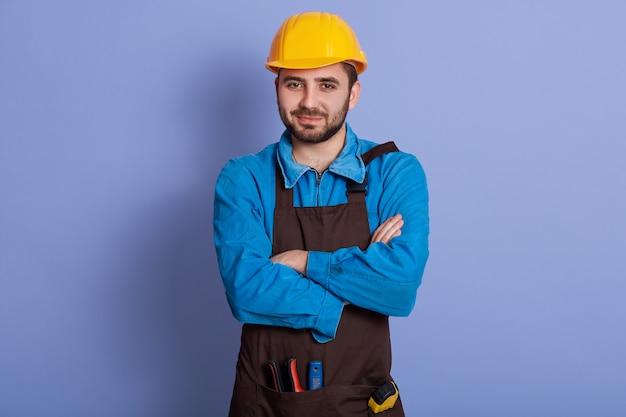 Porträt eines selbstbewussten starken jungen mechanikers, der arme verschränkt hat, helm und uniform trägt und direkt in die kamera schaut. arbeitstagskonzept.