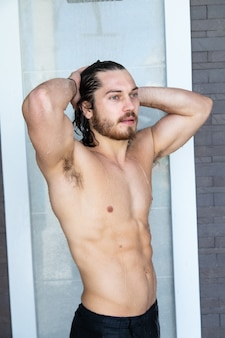 Porträt eines sexy gutaussehenden mannes, der am schwimmbad ruht. sommerferienkonzept.
