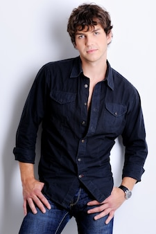 Porträt eines sexy hübschen jungen mannes, der im studio mit moderner lockiger frisur aufwirft