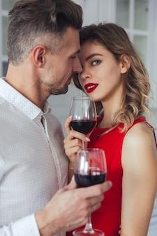 Porträt eines sinnlichen romantischen intelligenten gekleideten paartrinkens