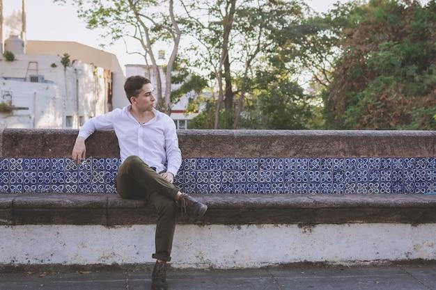 Porträt eines sitzenden jungen mannes mit nachdenklicher haltung mann, der auf einer steinbank sitzt und denkt