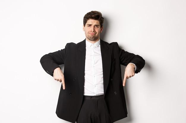 Porträt eines skeptischen und nicht amüsierten bärtigen mannes, der mit enttäuschtem gesicht mit den fingern nach unten zeigt, im anzug steht und sich beschwert